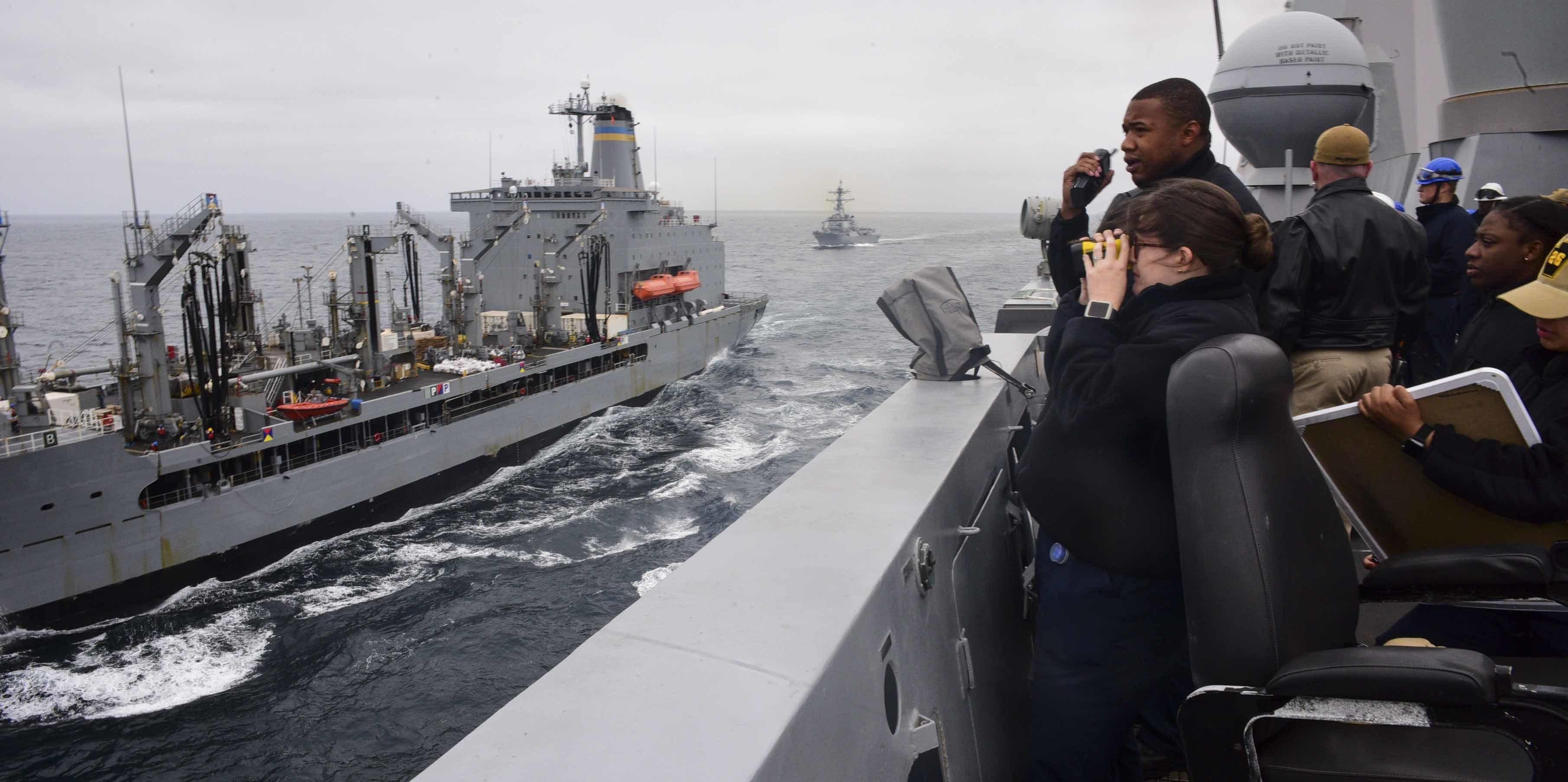 Sailors aboard the amphibious transport dock ship USS John P. Murtha (LPD 26) stand watch on the bridge