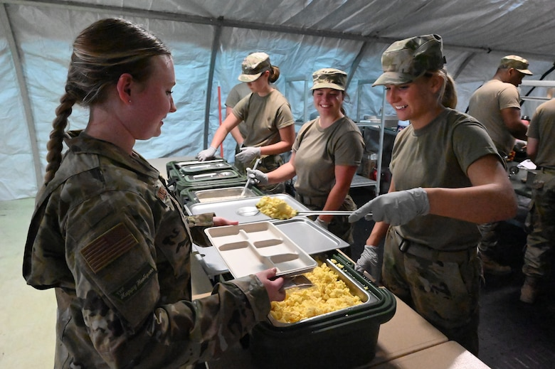 Three female military members dish food onto a tray inside a tent for another female military member at the North Dakota Air National Guard Base, Fargo, N.D., June 4, 2021.