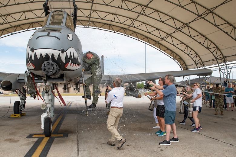 A photo of  Lieutenant Colonel Rob Sweet climbing out of an aircraft as his friends and family spray him with champagne