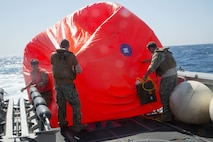 """210602-A-MU580-1061 ARABIAN GULF (June 2, 2021) - Sailors assigned to Commander, Task Force (CTF) 56 deploy a """"killer tomato"""" inflatable target during a live-fire exercise as part of an air operations in support of maritime surface warfare (AOMSW) exercise in the Arabian Gulf, June 2. CTF 56 commands and controls the employment of tactical Navy expeditionary combat forces in order to maximize U.S. 5th Fleet's lethality throughout the maritime domain utilizing eight task groups whose missions range from explosive ordnance disposal and salvage diving, Army civil affairs, Naval construction forces and expeditionary logistics support, maritime interdiction operations and maritime security, and embarked security teams. (U.S. Army photo by Spc. Zion Thomas)"""