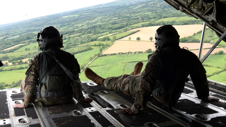 Airmen look out the back of a C-130J