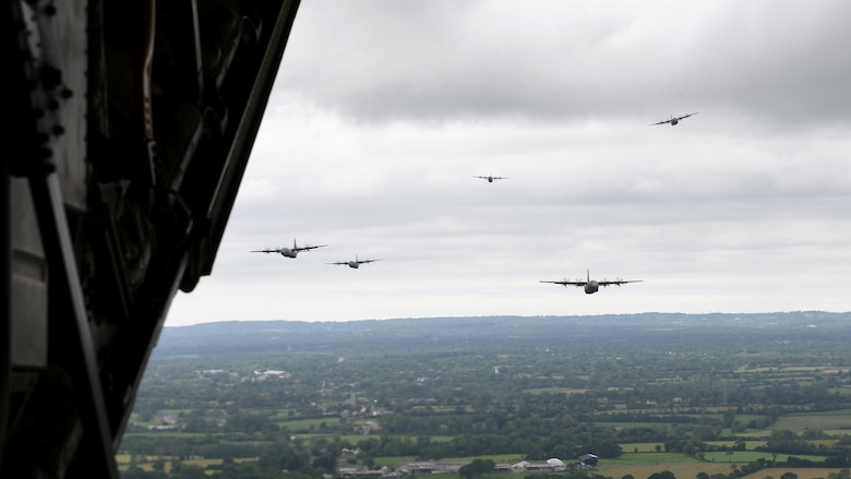 Aircraft fly in formation above Normandy, France.