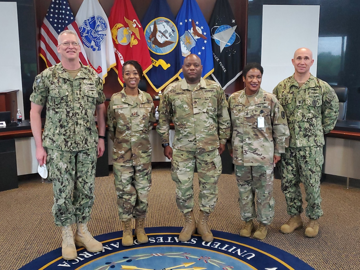 Four service members stand for a photo with flags in the background