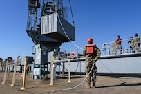 U.S. Soldiers from the 7th Transportation Brigade (Expeditionary) move shipping crates at 3rd Port, Joint Base Langley-Eustis, Virginia, March 9, 2021. The crates were loaded by crane onto a waiting barge to be transported to an exercise. (U.S. Air Force photo by Senior Airman Sarah Dowe)