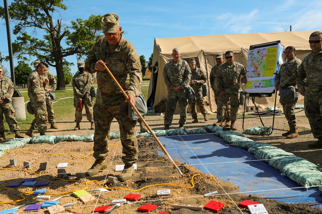 U.S. Army Reserve Maj. Richard Flores, 358th Civil Affairs Brigade points out major units and objectives during the Rehearsal of Concept drill, Command Post Exercise – Functional (CPX-F) 21-02 at Ft. McCoy, Wis., June 5, 2021.  Units from across U.S. Army Civil Affairs and Psychological Operations Command (Airborne) are working together at Ft. McCoy to improve readiness and staff interoperability in support of the U.S. Army Reserve's mission of a globally responsive force ready to deploy at a moment's notice.