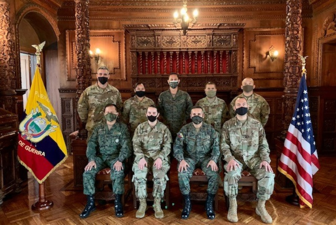 Eight military members pose for photo.