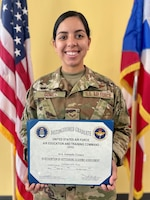 U.S. Air Force Senior Airman Amanda Gomez, from the 156th Operations Group, Host Nation Rider Flight, poses for a portrait holding the distinguished graduate award for completing the Basic Airborne Mission Systems Operator course with the highest grade average of the class, May 25, 2021 at the 156th Wing, Muñiz Air National Guard Base, Puerto Rico. The nine Airmen that graduated the course are the first qualified Host Nation Rider BAMSOs in the Puerto Rico Air National Guard. (U.S. Air National Guard photo by Tech. Sgt. Rafael D. Rosa)