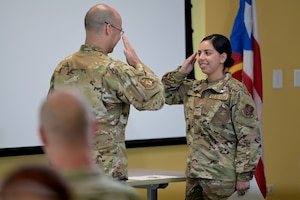 U.S. Senior Airman Amanda Gomez, with the 156th Operations Group, Host Nation Rider Flight, salutes Lt. Col. Raul Nieves, the 156th HNR officer in charge, after receiving his diploma for completing the Basic Airborne Mission Systems Operator course, May 25, 2021 at the 156th Wing, Muñiz Air National Guard Base, Puerto Rico. The nine Airmen that graduated the course are the first qualified Host Nation Rider BAMSOs in the Puerto Rico Air National Guard. (U.S. Air National Guard photo by Master Sgt. Caycee Watson)