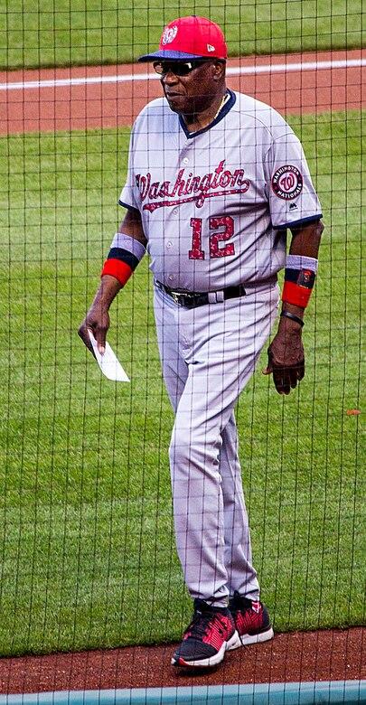 A man wearing a baseball uniform walks across a baseball field.