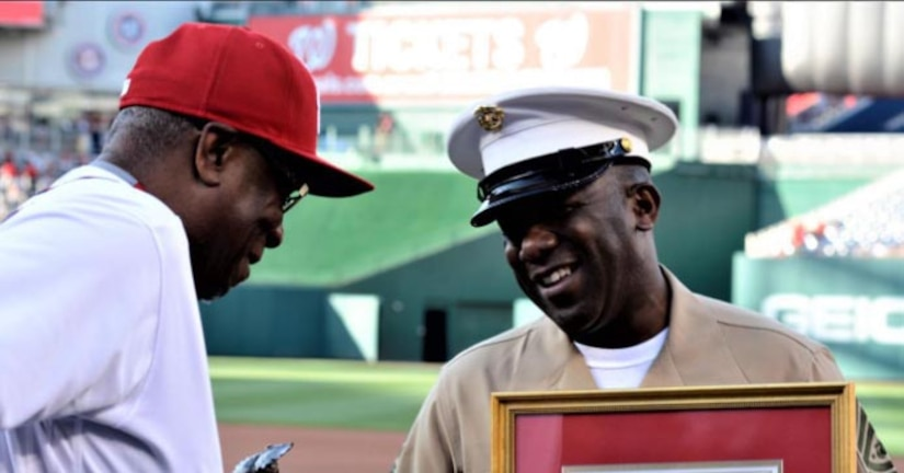A man wearing a baseball uniform looks at a framed document being held by a man wearing a military uniform.