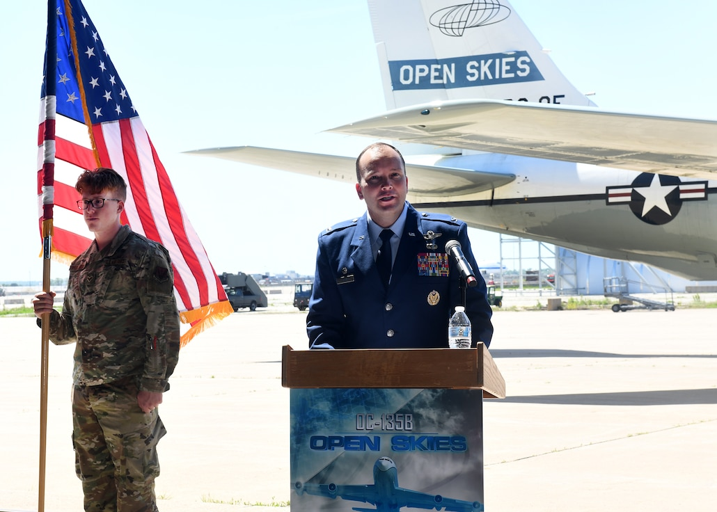 Man in Air Force uniform standing at a podium gives a speech. An Airman stands nearby holding the U.S. flag and the retiring aircraft is in the background.