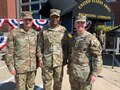 three men in army uniforms pose for a photo.