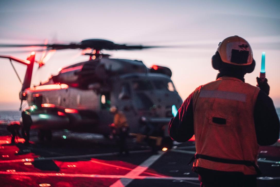 A U.S. Sailor signals a CH-53E Super Stallion before takeoff, aboard amphibious transport dock USS Portland (LPD 27), May 18.