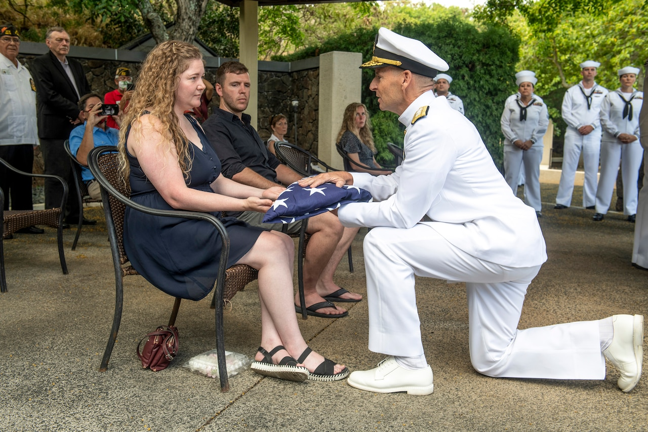 A kneeling sailor presents a folded U.S. flag to a civilian at an outdoor ceremony.