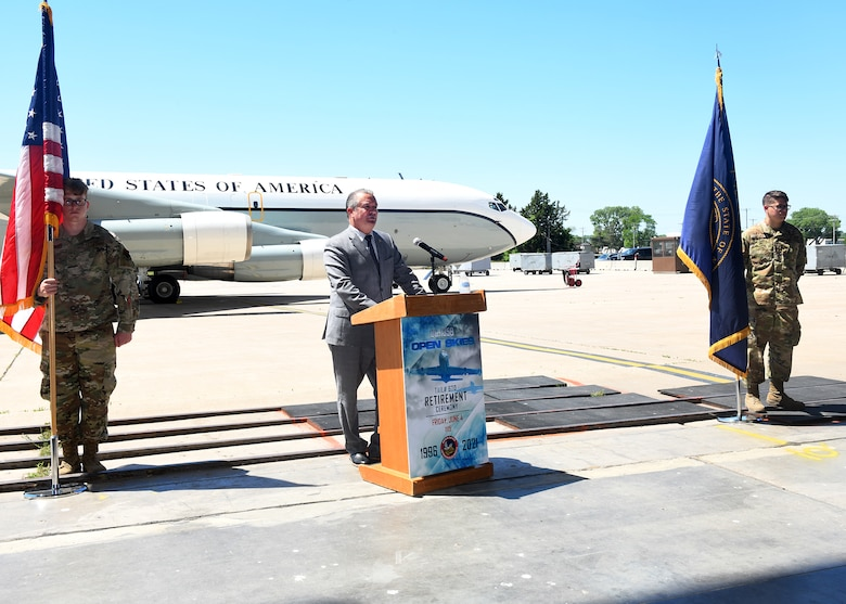 Man gives speech at a podium outside. An Airmen holding a flag stands on each side of the podium and the retiring OC-135 aircraft is in the background.