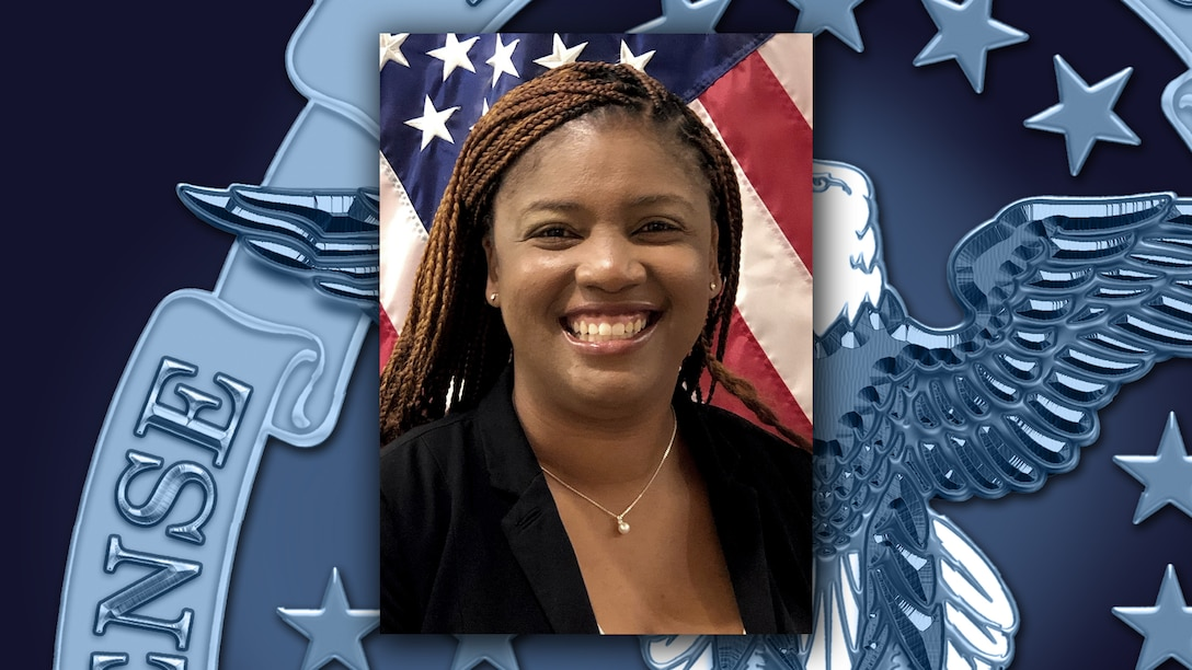 Head and shoulders picture of a Black woman in black shirt in front of the US flag.