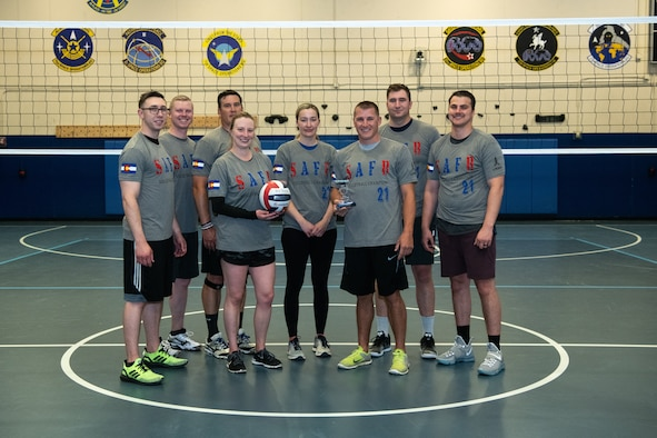 Members of Space Delta 8 – Satellite Communications and Navigational Warfare, 2nd Space Operations Squadron hold a plaque and volleyball to commemorate their victory in the intramural volleyball tournament at the Schriever Fitness Center at Schriever Air Force Base, Colorado on May 20, 2021. Teams did not compete in volleyball in 2020 due to the coronavirus pandemic, however, 2nd SOPS still managed to earn the title in this year's tournament. (U.S. Space Force photo by Kathryn Damon)
