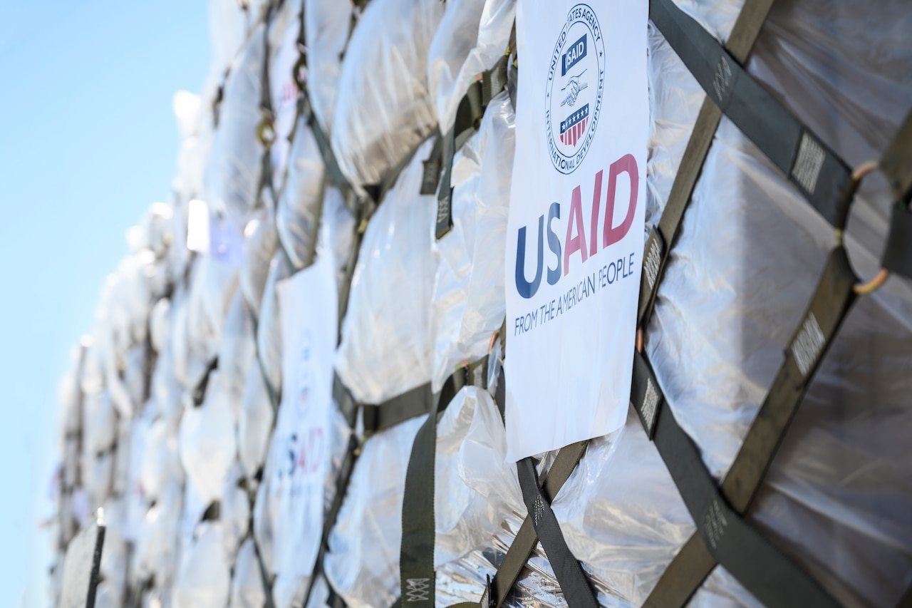 """Web mesh is wrapped around cargo. A paper sign reads """"USAID."""""""