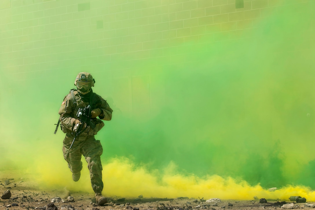 A guardsman runs through green smoke while holding a weapon.