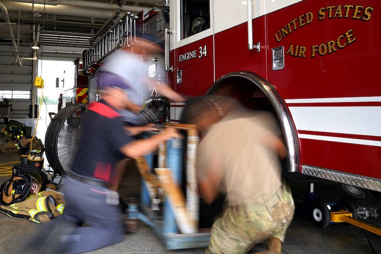 U.S. Air Force Airman 1st Class Kevin Munoz, 81st Civil Engineer Squadron firefighter, Dave Cleland, 81st CES crew chief, and Jerry Krumnow, 81st CES fire truck mechanic, replace a tire on a fire truck at the fire station at Keesler Air Force Base, Mississippi, June 2, 2021. The Keesler Fire Department responds to medical emergencies on and around base 24 hours a day. (U.S. Air Force photo by Senior Airman Seth Haddix)