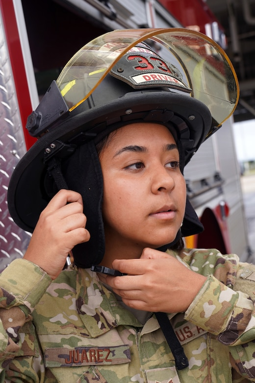 U.S. Air Force Airman 1st Class Cinthia Juarez, 81st Civil Engineer Squadron driver operator, puts on a fire protection helmet outside the fire station at Keesler Air Force Base, Mississippi, June 2, 2021. The Keesler Fire Department responds to medical emergencies on and around base 24 hours a day. (U.S. Air Force photo by Senior Airman Seth Haddix)