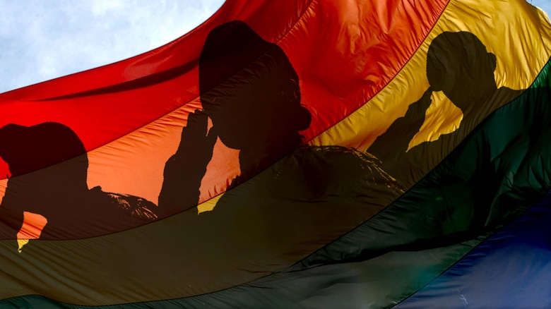 A graphic with servicemember silhouettes saluting over an LGBTQ+ flag.