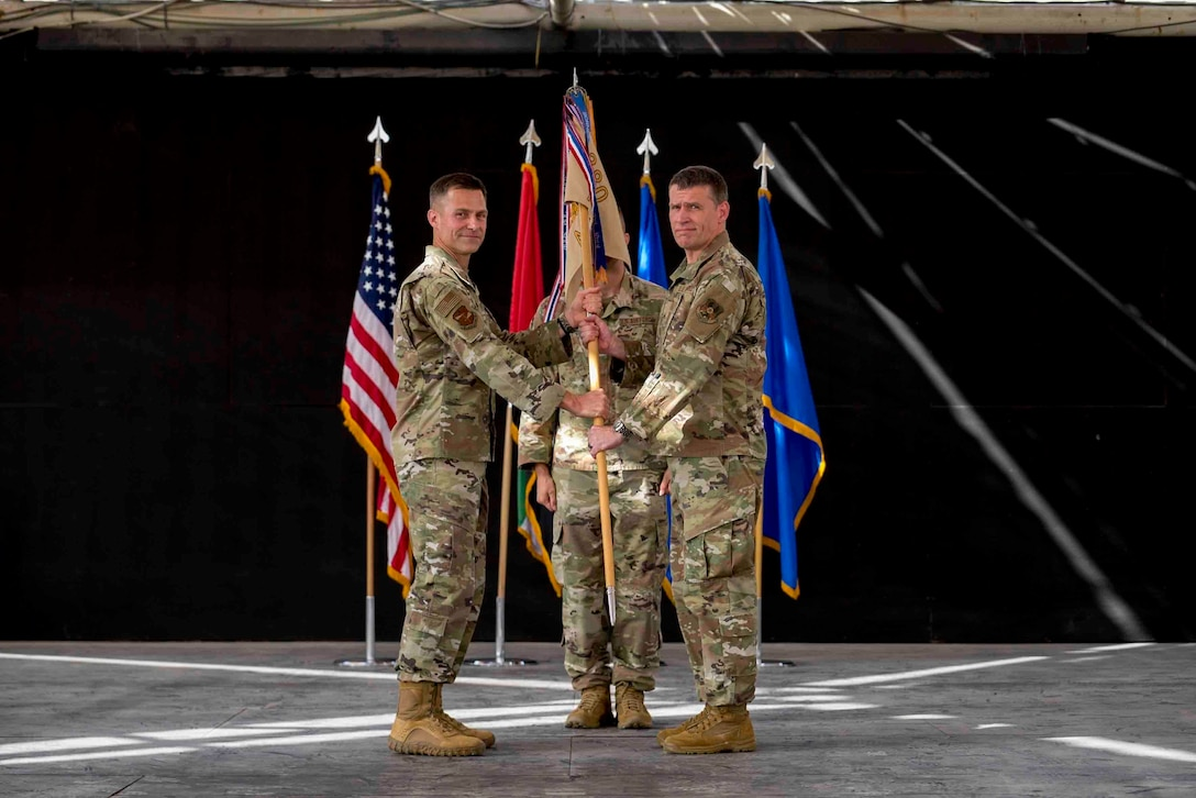 U.S. Air Force Brig. Gen. Larry Broadwell, outgoing commander, passes command of the 380th Air Expeditionary Wing to Brig. Gen. Andrew Clark, incoming commander, during a change of command ceremony at Al Dhafra Air Base, United Arab Emirates, June 8, 2021. The change of command ceremony is a military tradition that represents a formal transfer of authority and responsibility for a unit from one commanding officer to another.
