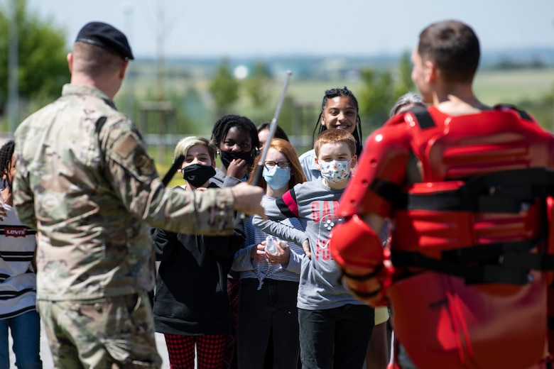 U.S. Air Force Airmen demonstrate advance baton techniques to onlookers.