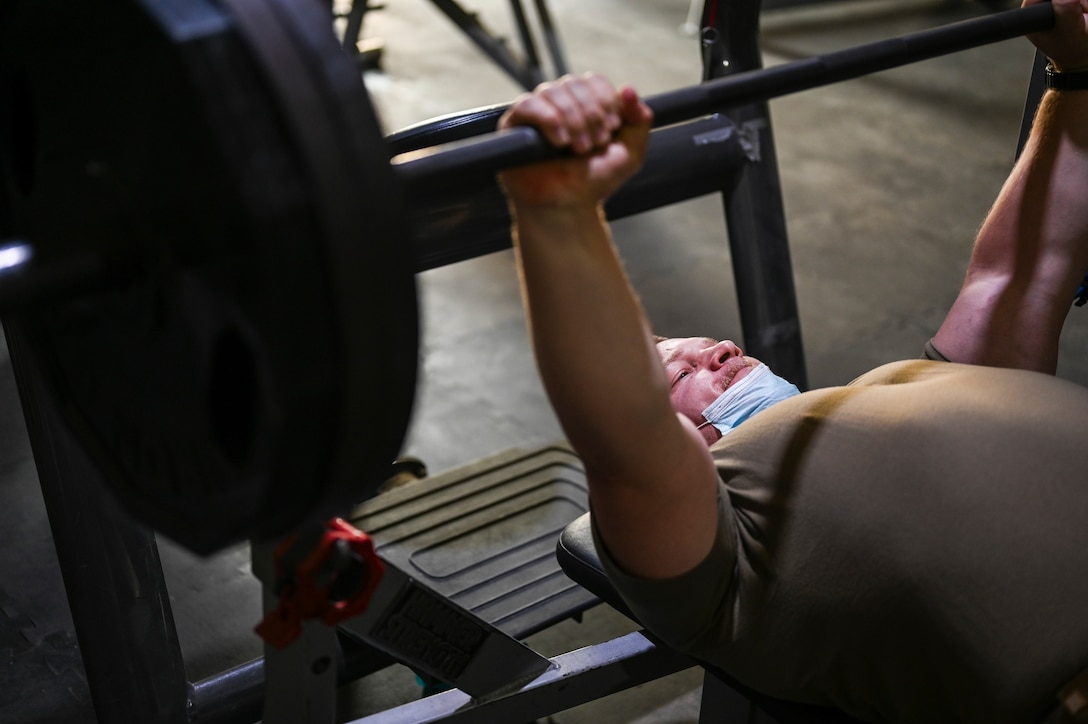 A photo of an Airman lifting weights.