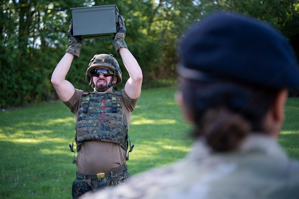 A member of the German Bundeswehr Military Police does overhead presses with a weighted ammo can as part of the Defender Challenge at Spangdahlem Air Base, Germany, June 2, 2021.