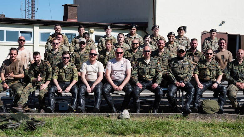 U.S. Air Force Airmen from the 52nd Security Forces Squadron and military police assigned to Germany's Feldjäger Regiments 1 and 2 sit for a group photo at Spangdahlem Air Base, Germany, June 2, 2021.