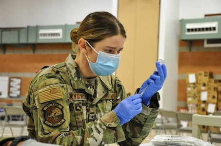 Nevada Air National Guard 1st Lt. Caleena Longworth with Joint Task Force 17 prepares a syringe with the Moderna vaccine at the Las Vegas Readiness Center, Wednesday, Jan. 27, 2021 in Las Vegas, Nevada. Longworth has vaccinated 4,500 people.