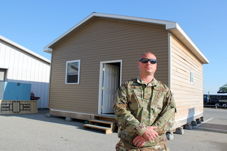 Master Sgt. Derek Leppek stands outside a small B-Hut, or barracks hut, style building at Selfridge Air National Guard Base, Mich., June 6, 2021. Leppek oversaw the creation of the temporary building, which will be used by the 127th Civil Engineer Squadron for hands-on construction trades training at the base. (U.S. Air Force photo by Master Sgt. Dan Heaton)