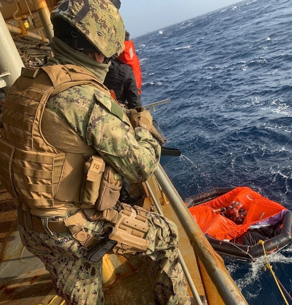 Master-at-Arms 2nd Class Michael Garcia, assigned to Embarked Security Intelligence Team 11, deployed with Commander, Task Force (CTF) 56, aboard the Military Sealift Command fleet replenishment oiler USNS Patuxent (T-AO 201), relays information on a radio during rescue operations for the crew members of a motor vessel Falcon Line, which sank in the Gulf of Aden, June 8.