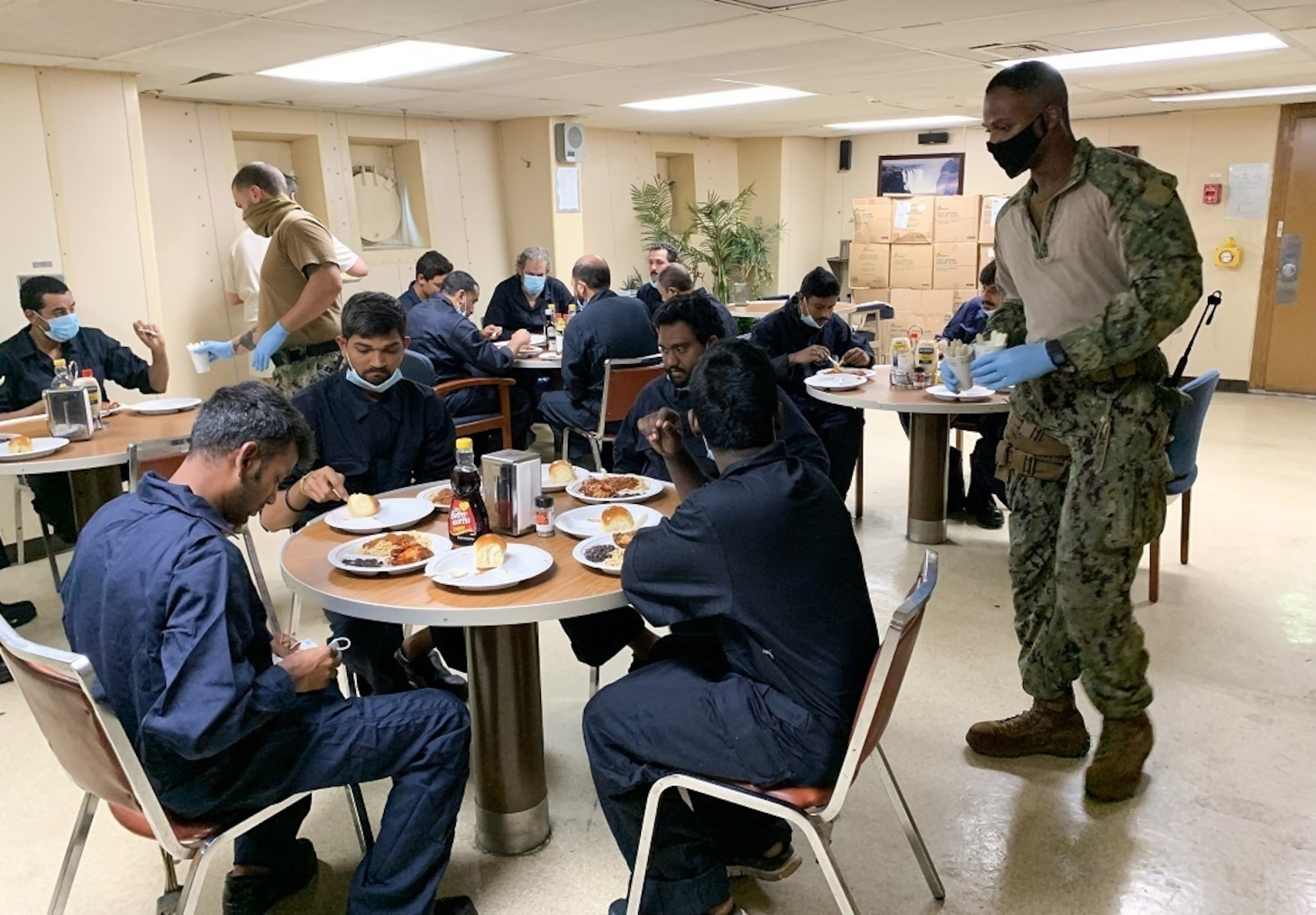 Gunner's Mate 1st Class Magezi Johnson and Master-at-Arms 3rd Class Gurney White, assigned to Embarked Security Intelligence Team 11, deployed with Commander, Task Force (CTF) 56, aboard the Military Sealift Command fleet replenishment oiler USNS Patuxent (T-AO 201), serve hot meals to rescued crew members from motor vessel Falcon Line, while underway in the Gulf of Aden, June 8.