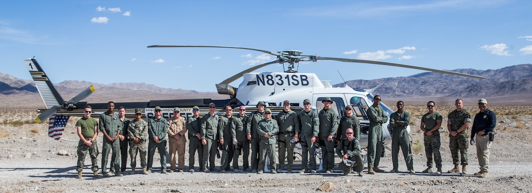 U.S. Marines with the Provost Marshal's Office, Marine Air Ground Task Force Training Command and San Bernardino County Sheriff's Department Deputies pose for a photo after a training exercise at Marine Corps Air Ground Combat Center, Twentynine Palms, California, June 1, 2021. The training was conducted to familiarize the Sheriff's Department with aerial with moving ground targets and to improve the partnership between the MCAGCC and local law enforcement. (U.S. Marines Corps photo by Lance Cpl. Gustavo Romero)