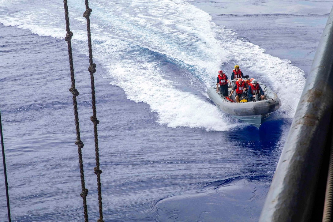 Sailors travel through waters in a small inflatable boat.