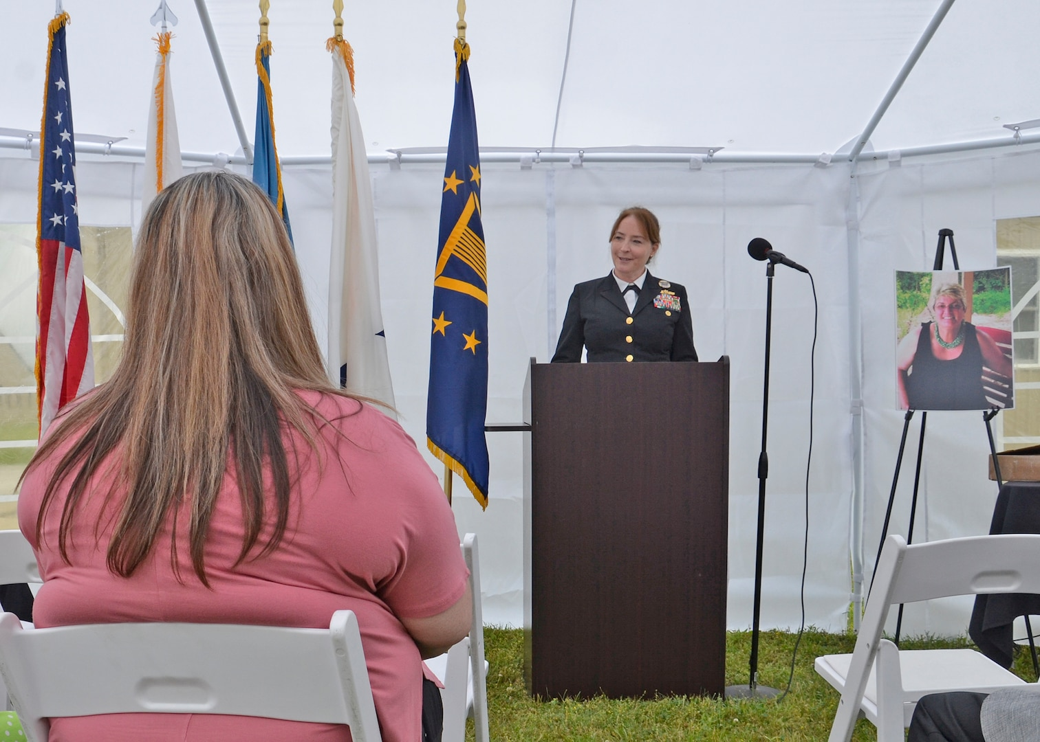 A Navy admiral speaks to listeners inside of a white tent.