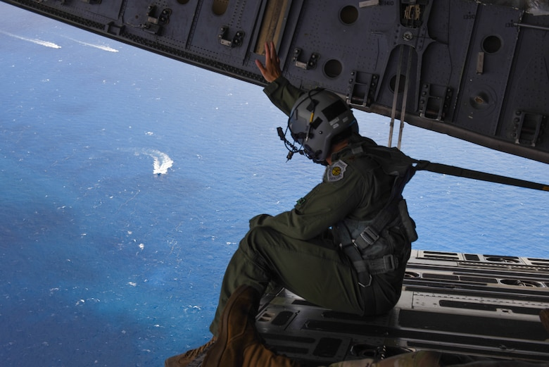 U.S. Air Force Maj. Mack Delgado, C-17 West Coast Demo Team pilot, waves to boats off the coast of Miami Beach, Florida, from the cargo ramp of a C-17 Globemaster III, May 31, 2021. The C-17 was headed back to Joint Base Lewis-McChord, Washington, after completing their demonstrations in the National Salute to Our Heroes Hyundai Air and Sea Show. (U.S. Air Force photo by Senior Airman Mikayla Heineck)