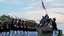 """Marines with the Silent Drill Platoon march for """"Pass in Review"""" during a Tuesday Sunset Parade at the Marine Corps War Memorial, Arlington, Va., June 8, 2021."""