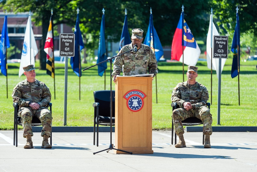 two men sitting wearing army uniforms, one man in uniform standing at a podium.