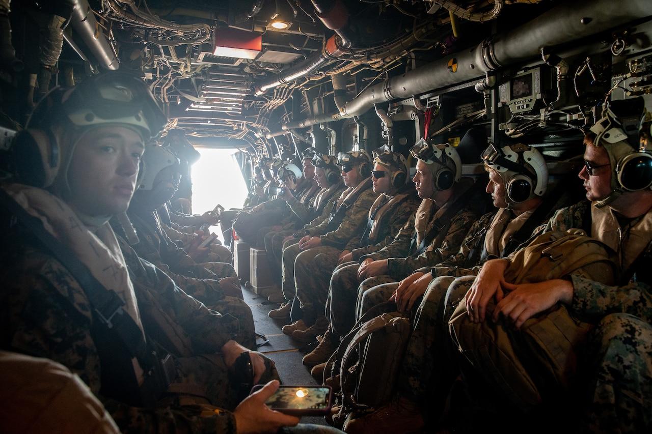 U.S. Marines, Australian service members sit aboard a V-22 Osprey.