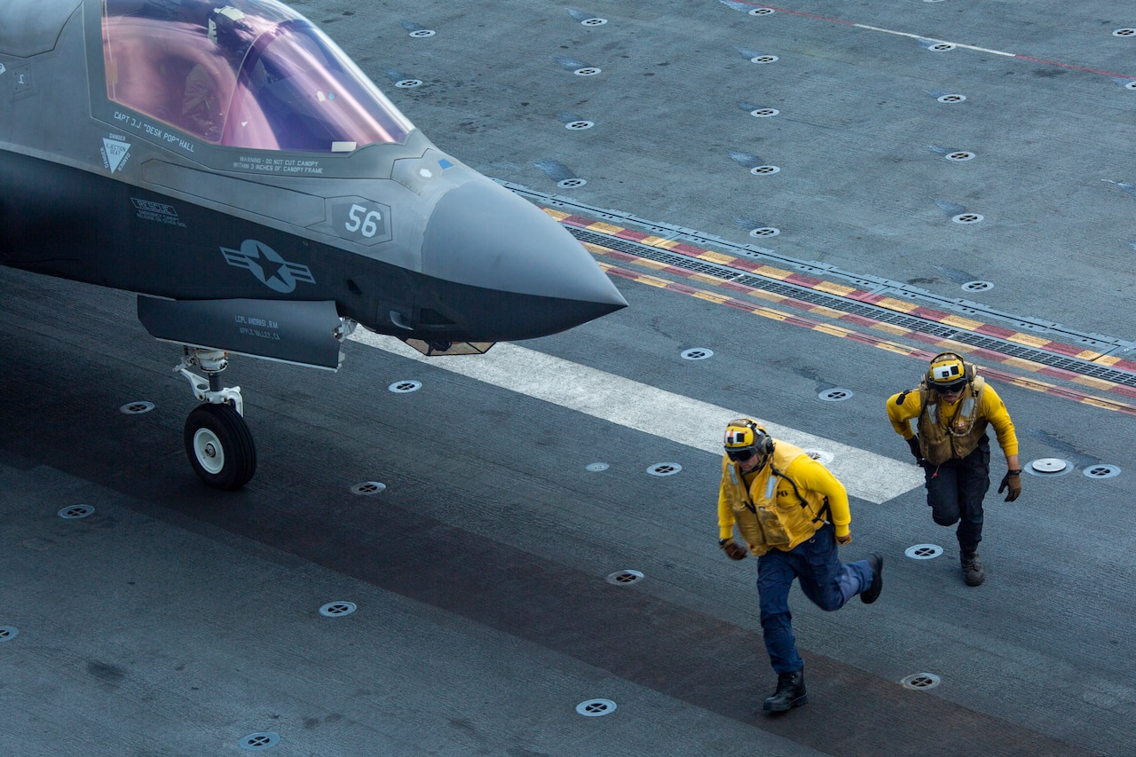 Sailors run in front of an F-35 aircraft readying for take off from the USS Makin Island.