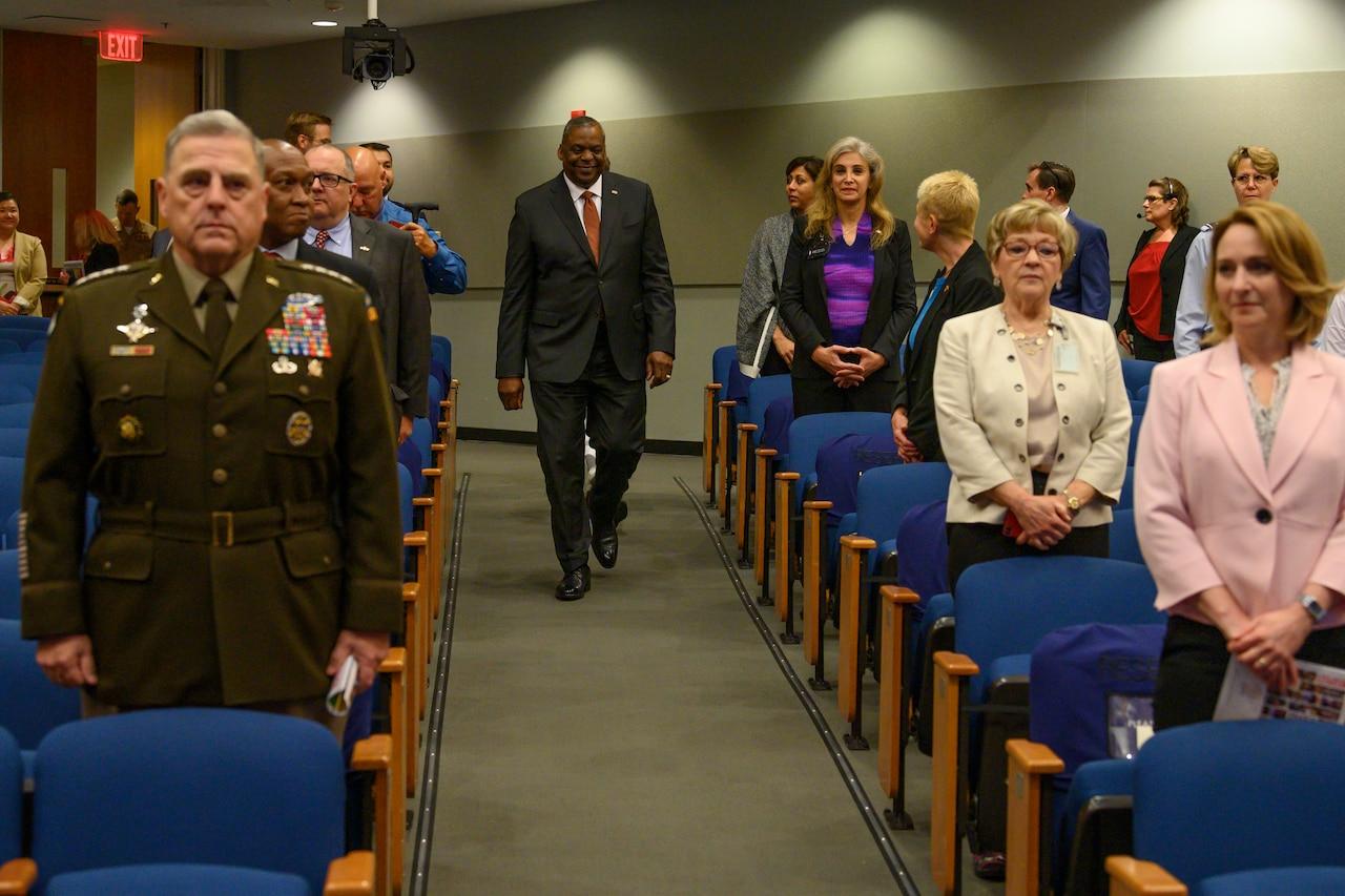Secretary of Defense Lloyd J. Austin III walks down an aisle in an auditorium.