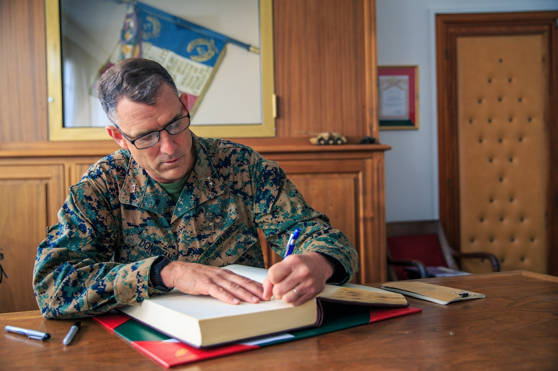 U.S. Marine Corps Maj. Gen. Francis Donovan, commanding general, 2d Marine Division, signs the guest book for the 1st Foreign Cavalry Regiment, 6th Light Armoured Brigade, in Compiegne, France, June 2, 2021. Donovan's visit to France included engagements with key leaders to strengthen relationships with the French Armed Forces in order to refine interoperability for future cooperation. (U.S. Marine Corps photo by Sgt. Margaret Gale)
