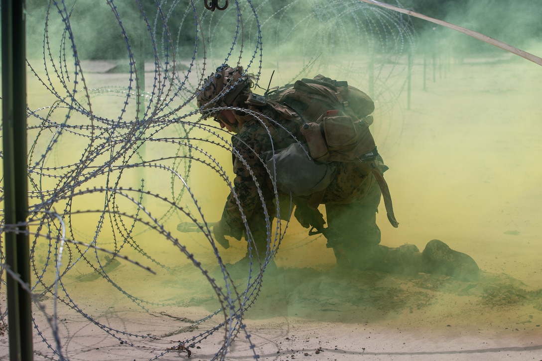 U.S. Marine Corps Pfc. Austin Pierce, a combat engineer with 2d Combat Engineer Battalion, 2d Marine Division, mechanically breaches a concertina wire obstacle during a demolition range as part of a Marine Corps Combat Readiness Evaluation on Camp Lejeune, N.C., June 7, 2021.