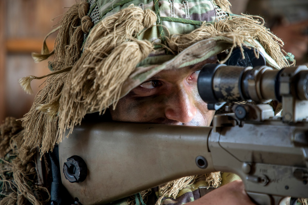 A soldier wearing a camouflage cover with mock foliage looks through the scope of a weapon.