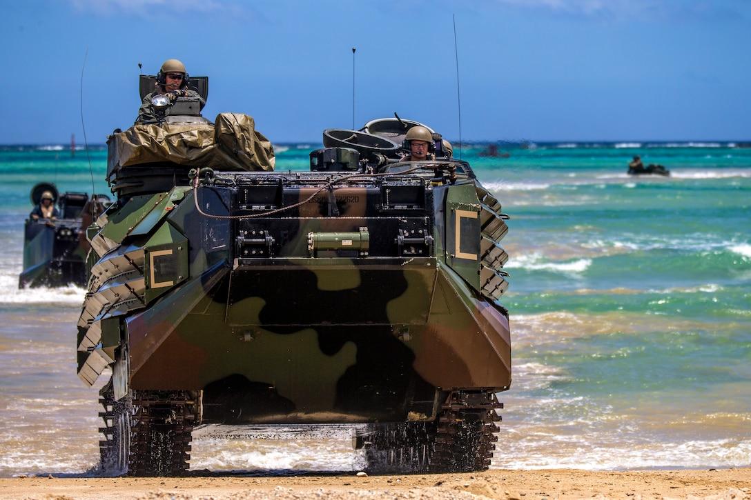 Marines travel in assault amphibious vehicles on a beach.