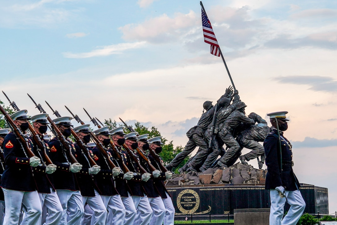 A statue showing Marines raising the American flag on Iwo Jima is framed by marching Marines.