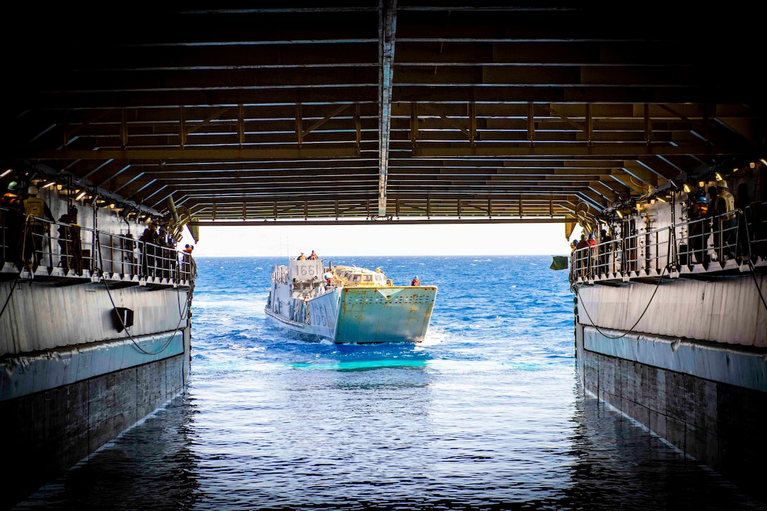 A utility landing craft enters the well deck of a ship.